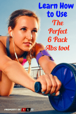 Young athletic woman using an Ab Wheel while wearing a fitness tracker on her arm and earbuds